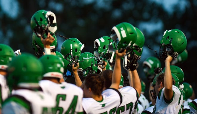 The Pierre T.F. Riggs Governors raise their helmets before a punt during their game against West Central on Friday, September 6, in Hartford.