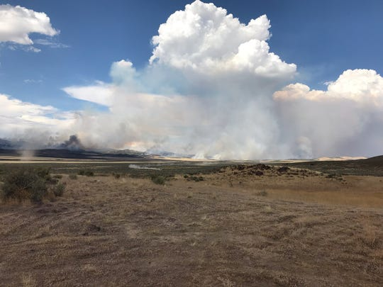 "Smoke rises from the ""Neck Fire,"" a wildfire in Iron County that had grown to more than 17,000 acres as of early Saturday."
