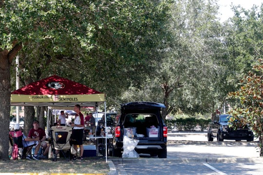 A group tailgates in the parking lot by the baseball field before kickoff Saturday, Sept. 7, 2019.
