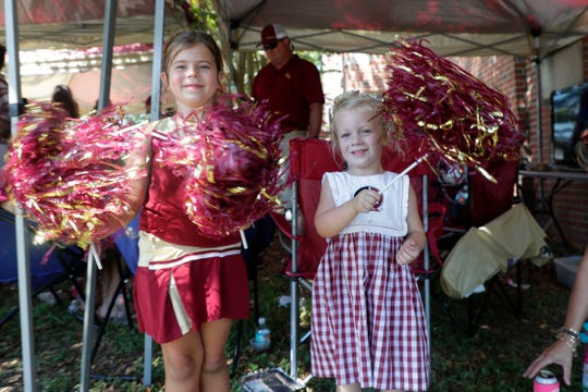 Ava Paolercio, 5, and her friend Quinn Dunagan, 4, shake their pom-poms at a tailgate before kickoff Saturday, Sept. 7, 2019.