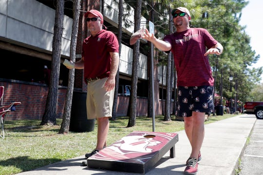 Travis Kelly, left, and Blake Womble play corn hole at a tailgate with their friends Saturday, Sept. 7, 2019.