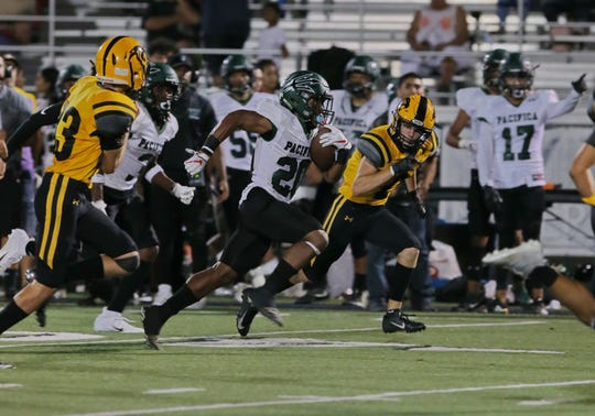 Pacifica's Malik Sherrod races past the Newbury Park defense to score a touchdown in the second quarter of the Tritons' 65-14 victory on Friday night.