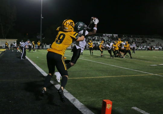 Pacifica's Nohl Williams intercepts a pass at the goal line before racing 100 yards for a touchdown near end of second quarter during the Tritons' 65-14 win over host Newbury Park on Friday night.