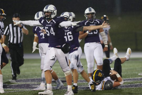 John Jay's Lucas Colette (54) celebrates after stopping Lourdes Mario Hickey (4) during football action at John Jay High School in Cross River Sept. 6, 2019.  John Jay won the game 42-21.