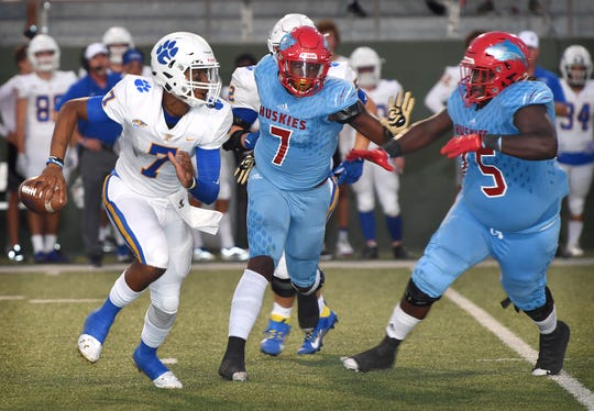Frenship Tigers quarterback Donovan Smith (7) is pursued by Hirschi defensemen Chris Murray (7) and JT Taylor (75) in second quarter action Friday night at Memorial Stadium.