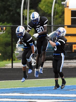 Jeremiah Norman, left, is met in the end zone by Jamal Wiggins and Jordan Martin after catching a touchdown pass in the first quarter of a 35-25 win against Johnstown on Friday at John D. Sulsberger Memorial Stadium.