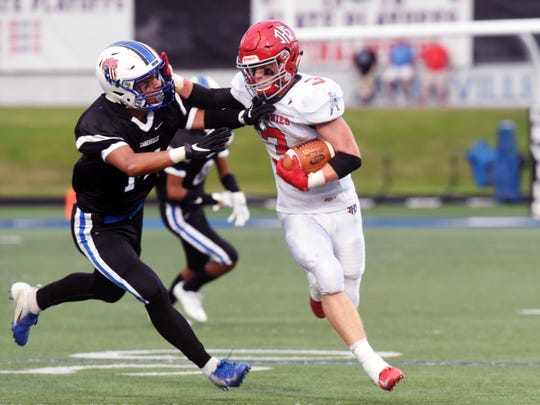 Junior Wes Myers stiff-arms Zanesville's Casey Cassell during the Johnnies' 35-25 loss on Friday night at John D. Sulsberger Memorial Stadium. Myers ran 33 times for 173 yards.