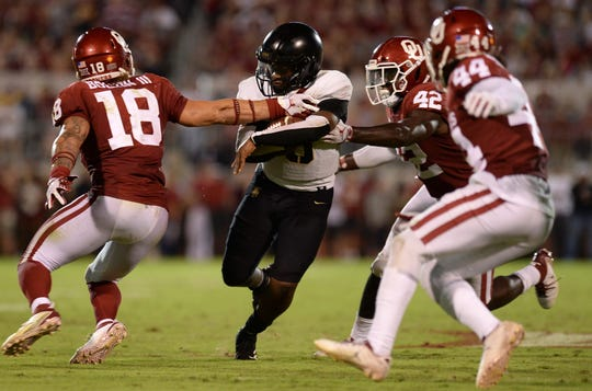 Army quarterback Kelvin Hopkins Jr. tries to break a tackle against Oklahoma during their game in 2018.