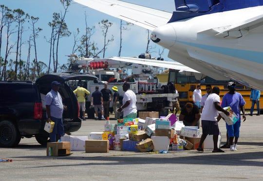 Sep 7, 2019; Treasure Cay, Bahamas;  People unload humanitarian aid at the Treasure Cay Airport on Treasure Cay in the Bahamas following the passage of Hurricane Dorian.
