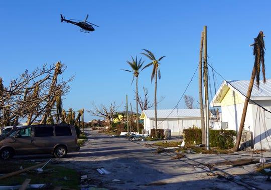 Sep 7, 2019; Treasure Cay, Bahamas; A helicopter flies over homes damaged by Hurricane Dorian on Treasure Cay in The Bahamas.