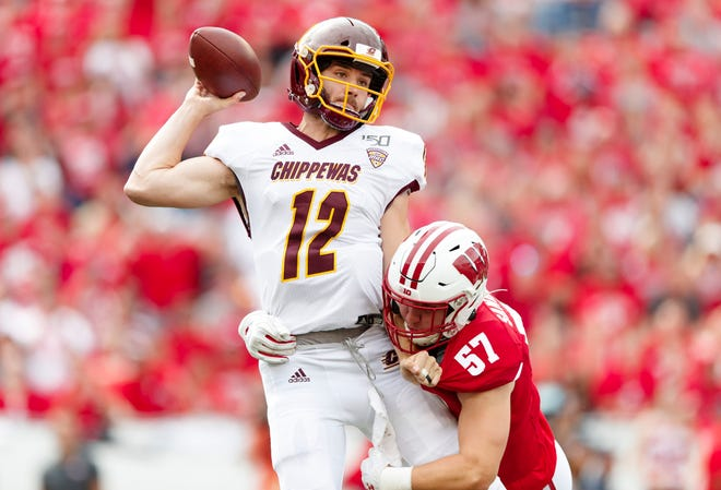 Central Michigan Chippewas quarterback Quinten Dormady (12) throws a pass under pressure of Central Michigan Chippewas defensive lineman NeVen Simington (57) during the first quarter at Camp Randall Stadium.