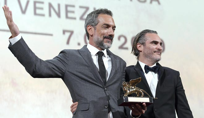US director Todd Phillips (L) holds the Golden Lion award for his movie 'Joker' as he poses US actor Joaquin Phoenix during the awarding ceremony of the 76th annual Venice International Film Festival on Sept. 7, 2019 in Venice.
