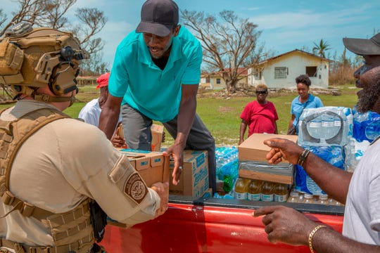 """In this image courtesy of US Customs and Border Protection (USCBP), USCBP agents deliver food and water to severely damaged Fox Town on the Abaco Islands in the Bahamas, on September 6, 2019, in the aftermath of Hurricane Dorian. - The death toll from Hurricane Dorian's devastating rampage across the Bahamas rose to 43 and was likely to climb """"significantly,"""" officials said, with hundreds missing even as rescuers plucked desperate survivors from the debris. Confirming the new toll of 43, Prime Minister Hubert Minnis said 35 were killed on worst-hit Abaco and eight on Grand Bahama island."""