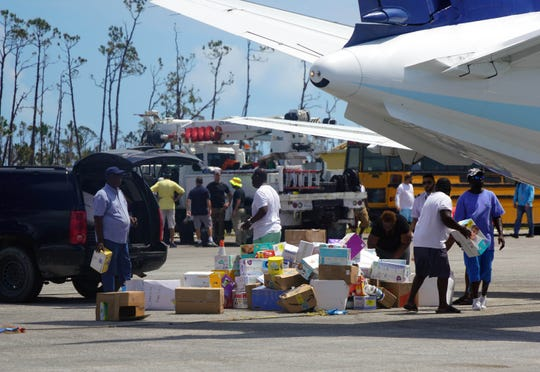 People unload humanitarian aid Sept. 7 at the Treasure Cay Airport in the Bahamas after the passage of Hurricane Dorian.