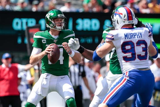 New York Jets quarterback Sam Darnold (14) drops back as Buffalo Bills defensive end Trent Murphy (93) defends during the first half at MetLife Stadium.