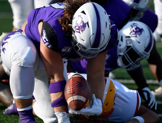 ACU defensive tackle Cole Burgess recovers the ball after it was knocked from the grasp of Arizona Christian quarterback Emilio Araize during Saturday's game at Abilene Christian University.