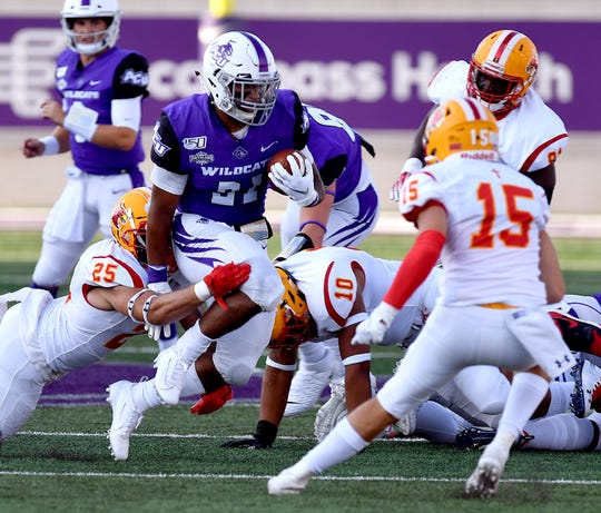 Arizona Christian defensive players try to bring down ACU running back Tracy James during the nonconference game Sept. 7 at Abilene Christian University's Wildcat Stadium.
