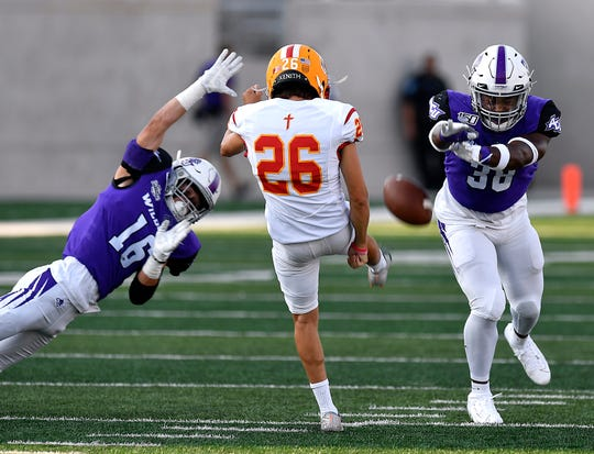 ACU defensive players Ryan Stapp (left) and Greg Green try to block the punt of Arizona Christian kicker Michael Corso during Saturday's game at Abilene Christian University.