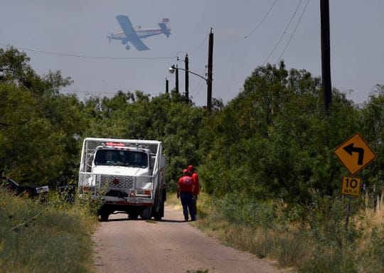 Firefighters watch a Texas A&M Forestry Service aircraft descend before dropping fire retardant on a grass fire Sunday north of U.S. Highway 277.