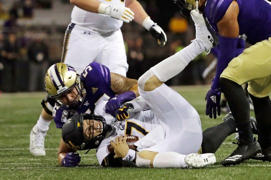 California quarterback Chase Garbers, center, is sacked by Washington linebacker Laiatu Latu, left, during the first half of an NCAA college football game, Saturday, Sept. 7, 2019, in Seattle.