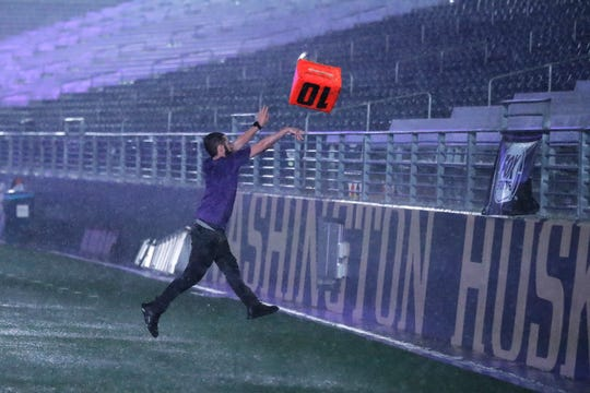 A fan takes advantage of a severe weather delay to throw a yardage marker into the stands at Husky Stadium during a weather delay in the first quarter of an NCAA college football game between Washington and California, Saturday, Sept. 7, 2019, in Seattle. The marker was later returned to the field.
