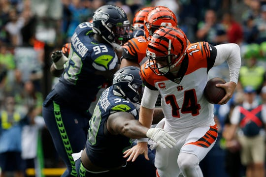 Cincinnati Bengals quarterback Andy Dalton (14) fights a tackle from Seattle Seahawks defensive tackle Quinton Jefferson (99) before being brought down in the second quarter of the NFL Week 1 game between the Seattle Seahawks and the Cincinnati Bengals at CenturyLink Field in Seattle on Sunday, Sept. 8, 2019.