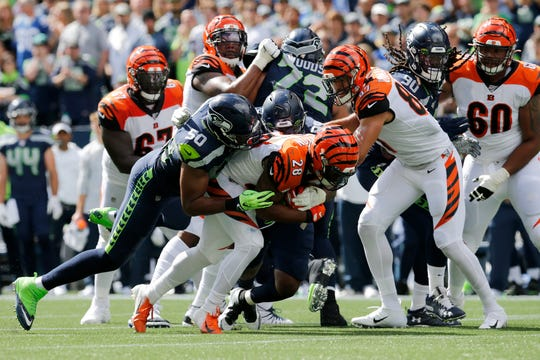 Cincinnati Bengals running back Joe Mixon (28) fights off tackles on a carry in the first quarter of the NFL Week 1 game between the Seattle Seahawks and the Cincinnati Bengals at CenturyLink Field in Seattle on Sunday, Sept. 8, 2019.