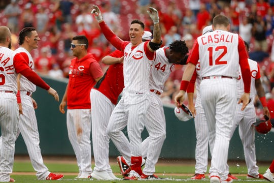 Cincinnati Reds' Michael Lorenzen, center, celebrates after hitting a game-winning RBI double off Arizona Diamondbacks relief pitcher T.J. McFarland in the ninth inning of a baseball game, Sunday, Sept. 8, 2019, in Cincinnati.