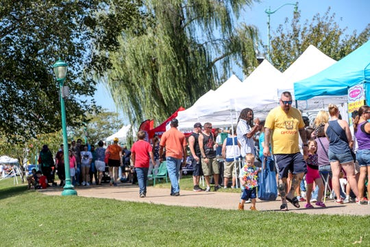 Patrons roam the pathway in the park leading them by different vendors during the Riverfest Music Festival at McGregor Park in Clarksville, Tenn., on Saturday, Sept. 7, 2019.