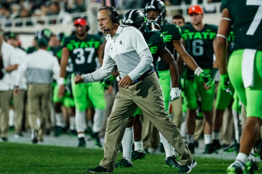 Michigan State head coach Mark Dantonio high-fives players after a touchdown against Western Michigan during the first half at Spartan Stadium in East Lansing, Saturday, September 7, 2019.
