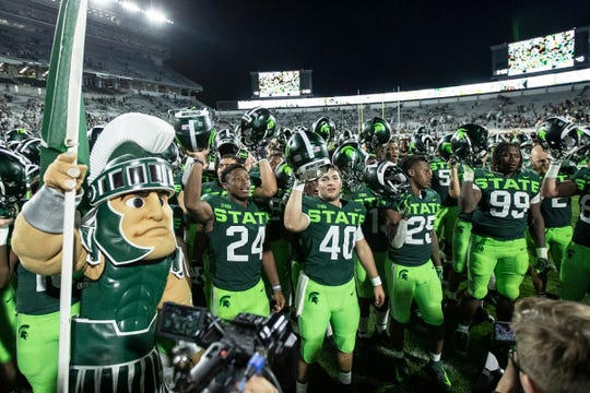 Michigan State players sing the fight song with Sparty, after the 51-17 win over Western Michigan.