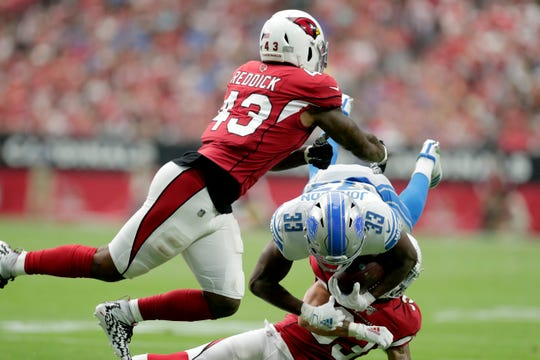 Kerryon Johnson is hit by Cardinals linebacker Haason Reddick (43) and cornerback Robert Alford during the first half.