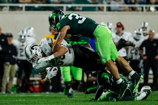Michigan State's Joe Bachie, top, tackles Western Michigan's Brett Borske during the first half at Spartan Stadium in East Lansing, Saturday, September 7, 2019.