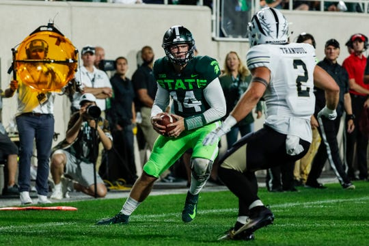 Brian Lewerke runs with the ball against Western Michigan during the first half at Spartan Stadium.