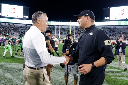 Michigan State coach Mark Dantonio, left, and Western Michigan coach Tim Lester shake hands after the game.