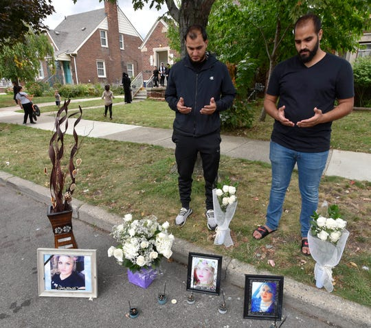 Mohammad Aljanabi, left, and Ali Aljanabi, brothers of shooting victim, Saja Aljanabi, says prayers at their sister's memorial.