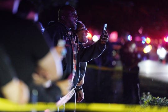A man takes photos with a cellphone at the scene of an officer-involved shooting on East 77th Street in Richfield, Minn., Saturday night.