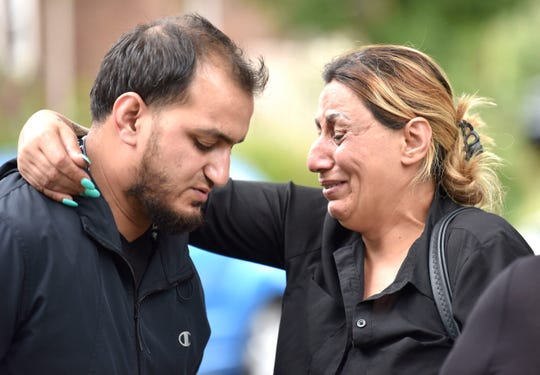 Close-family friend Zena Abbo, right, hugs Mohammad Aljanabi, brother of Saja Aljanabi, who was shot to death here, Friday night.   Family members and close-family friends mourn the loss of Saja Aljanabi, Sunday afternoon, September 8, 2019, as they light candles around her memorial on Bingham St. near Morross in Dearborn. Saja was shot to death while she sat in her brother's car, here, as she came to visit the family, Friday night.