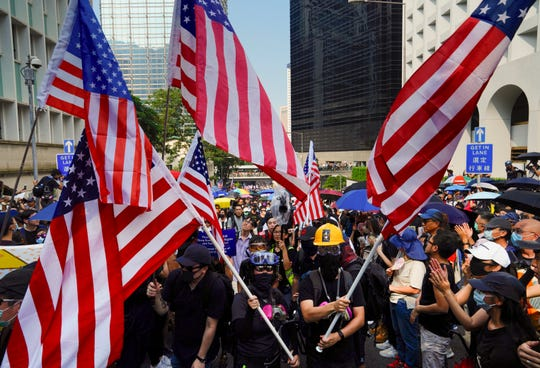Protesters shout slogans and wave U.S. flags as they march from Chater Garden to the U.S. Consulate in Hong Kong, Sunday.