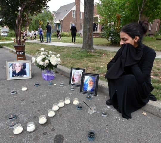 Zainab Aljanabi, sister of shooting victim Saja Aljanabi, puts her hands over her face as she cries at the make-shift memorial of her slain sister.