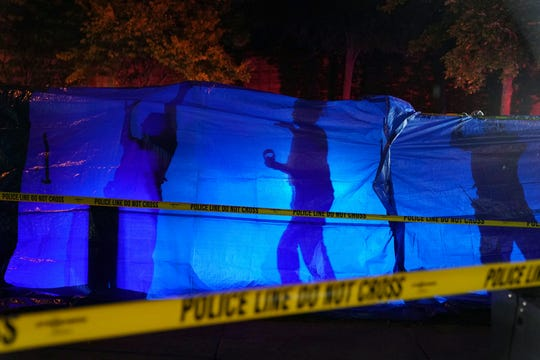 Police put up a blue tarp to block the view of a body at the scene of an officer involved shooting in Richfield, Minn., Saturday night.