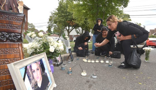 Close-family friend Zena Abbo, right, and others light candles at the make-shift memorial of her friend, Saja Aljanabi.  Family members and close-family friends mourn the loss of Saja Aljanabi, Sunday afternoon, September 8, 2019, as they light candles around her memorial on Bingham St. near Morross in Dearborn. Saja was shot to death while she sat in her brother's car, here, as she came to visit the family, Friday night.