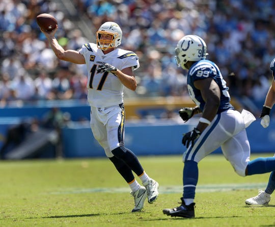 Los Angeles Chargers quarterback Philip Rivers (17) gets the ball away as he is pressured by Indianapolis Colts defensive end Justin Houston (99) in the second quarter of their game at Dignity Health Sports Park in Carson, CA., on Sunday, Sept., 8, 2019.