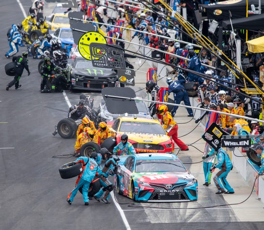 Crews work on the cars during a pitstop under yellow during the running of the 2019 Big Machine Vodka 400 at the Brickyard at Indianapolis Motor Speedway, Sunday, Sept. 8, 2019.