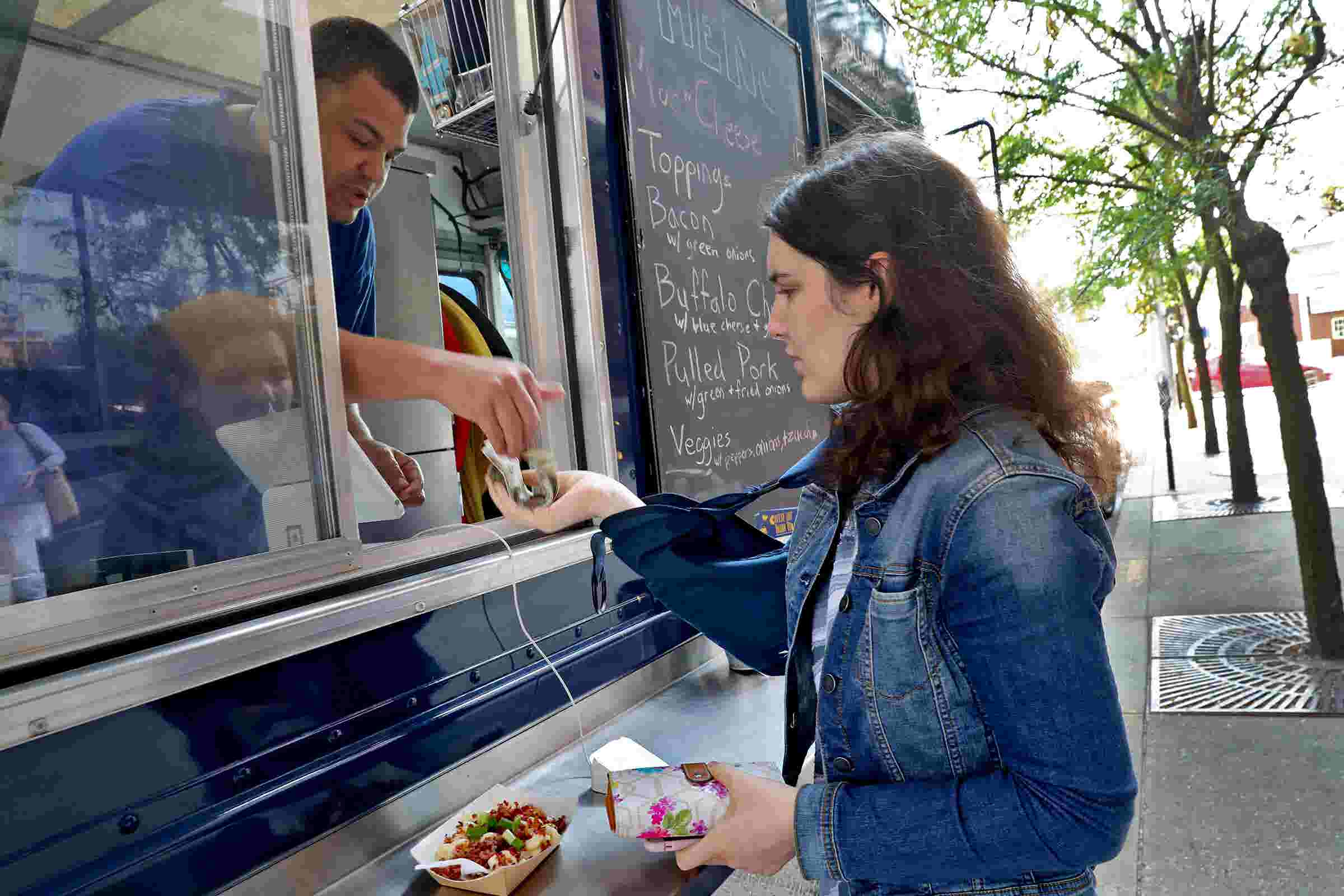 Food truck serves mac and cheese to guests and careers to disabled adults