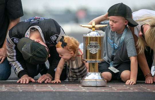 Monster Energy NASCAR Cup Series driver Kevin Harvick (4) kisses the bricks with his daughter Piper Harvick, their son Keelan Harvick and his wife DeLana Lynn Harvick, after winning the 2019 Big Machine Vodka 400 at the Brickyard at Indianapolis Motor Speedway on Sunday, Sept. 8, 2019.