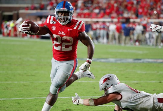 Ole Miss running back Scottie Phillips (22) holds out his arm as he scores on a 1-yard touchdown run past a fallen Arkansas defender during the second half of their NCAA college football game, Saturday, Sept. 7, 2019, in Oxford, Miss.
