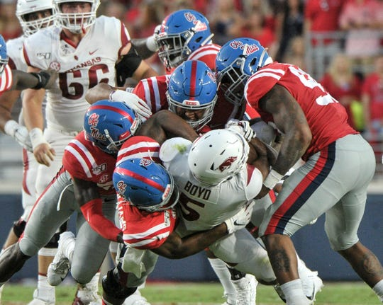 Sep 7, 2019; Oxford, MS, USA; Arkansas Razorbacks running back Rakeem Boyd (5) is tackled by Ole Miss linebacker Sam Williams (13) during the first half at Vaught-Hemingway Stadium. Mandatory Credit: Justin Ford-USA TODAY Sports