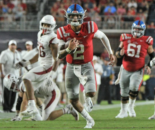 Ole Miss quarterback Matt Corral carries the ball against Arkansas defensive lineman Zach Williams (56) during the first half Saturday at Vaught-Hemingway Stadium in Oxford.
