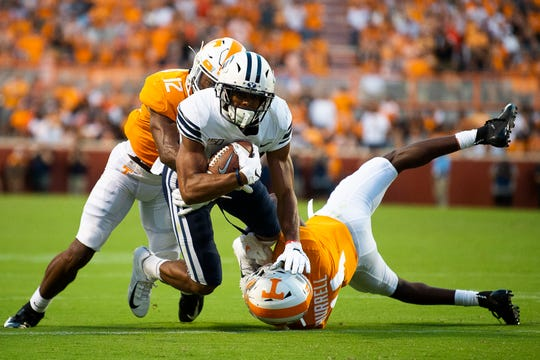 BYU wide receiver Micah Simon (13) is tackled by Tennessee defensive back Shawn Shamburger (12) and Warren Burrell (4) during Saturday's game. Simon later had a 64-yard catch-and-run to set up the tying field goal.